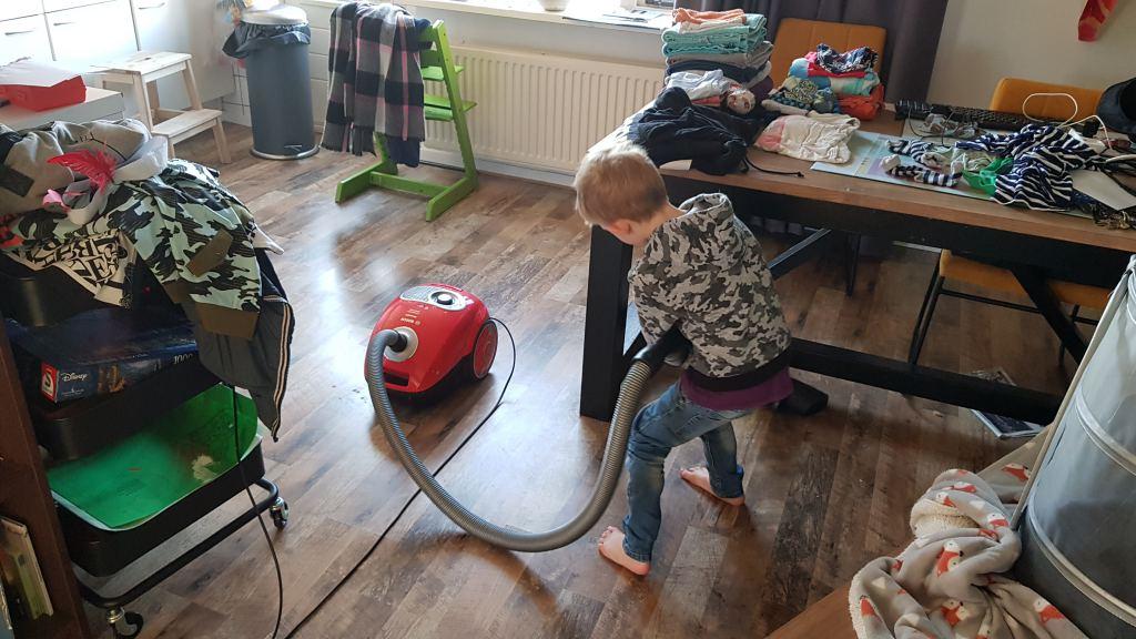 kind helpt met stofzuigen